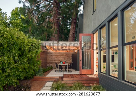 Open doors leading into contemporary home with wooden terrace and illuminated seating arrangement, open floor plan and greenery at night. Large window showing modern interior at twilight.  - stock photo