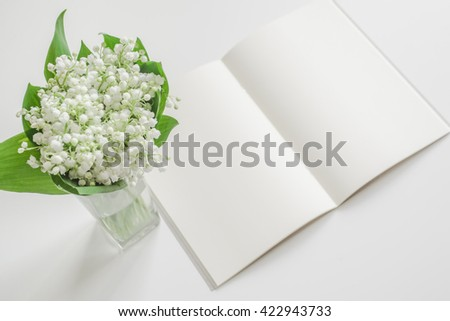 Open empty book with lily of the valley on the bowl. Blank pages with spring flowers bouquet. - stock photo
