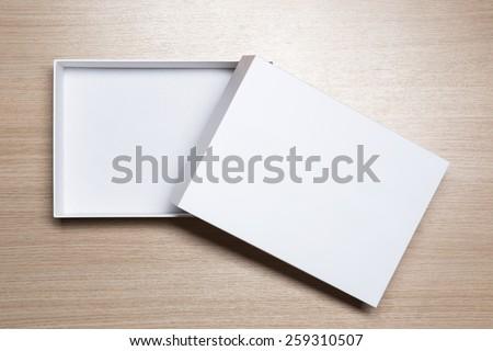 Open empty white box on wooden table - stock photo