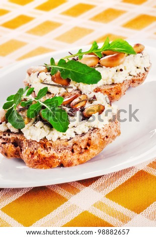 Open faced sandwices with goat cheese, almonds and arugula, shallow dof - stock photo