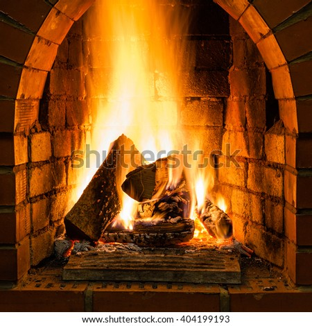 open fire in fire-box of brick fireplace in country cottage - stock photo