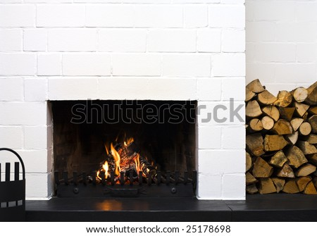 open fireplace in a living-room, stacked wood at side - stock photo