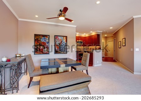 Open floor plan in modern apartment. View of dining area and bright burgundy kitchen room - stock photo