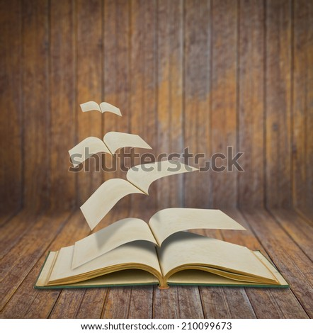 Open flying old books in wood room - stock photo