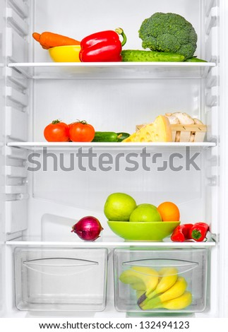 open fridge with fresh vegetables - stock photo