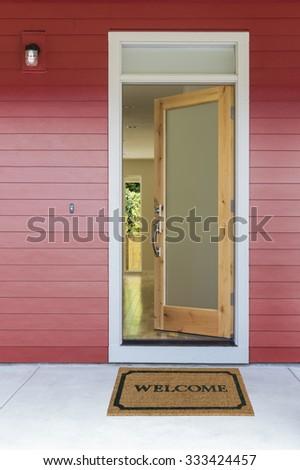 Open front door with welcome mat - stock photo