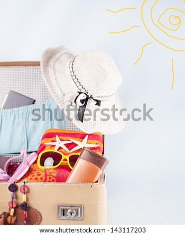 open full suitcase full of holiday stuff on blu bakcground - stock photo