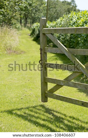 Open gate to grass pathway on a summers day. - stock photo
