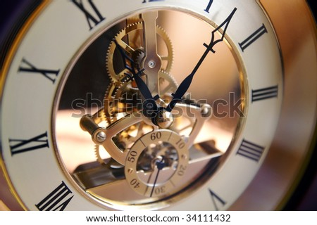 Open-gearing clock on a table, blur, shadows and lights - stock photo