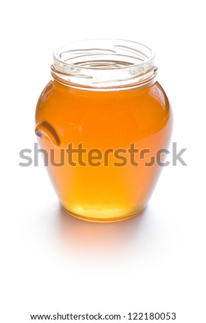 Open glass jar full of honey isolated on white background - stock photo