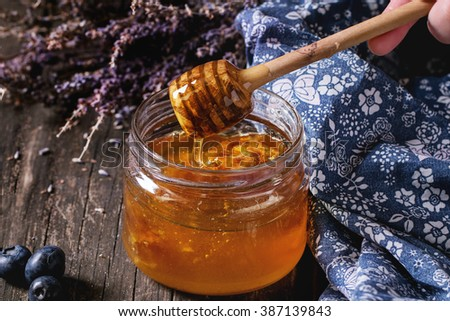 Open glass jar of liquid honey with honeycomb inside, flowing honey from honey dipper, fresh blueberries and bunch of dry lavender over old wooden table with blue textile rag. Dark rustic style - stock photo