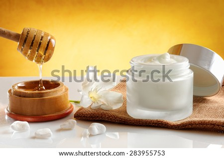 Open glass pot with honey moisturizer isolated on white glass table.  Flower, burlap and cane with honey container decoration. Front view. Yellow gradient background - stock photo