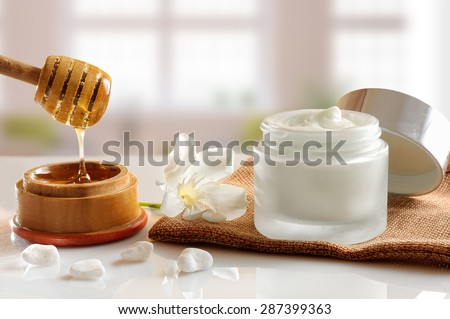 Open glass pot with honey moisturizer isolated on white glass table.  Flower, stones, burlap and cane with honey container decoration. Front view with background windows - stock photo