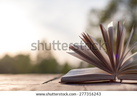 Open hardback book, fanned pages on wood planks. Summer spring background with open book. Back to school. Copy Space. Education background. - stock photo