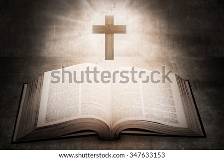 Open holy bible with wooden cross in the middle. Christian concept - stock photo