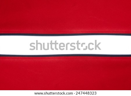 Open horizontal zipper on red material against white background