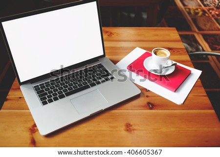 Open laptop computer with blank copy space screen for your information content or text message, portable net-book with cup of cappuccino lying on wooden table in contemporary coffee shop interior  - stock photo