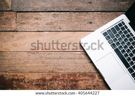 Open laptop on old wooden table - stock photo