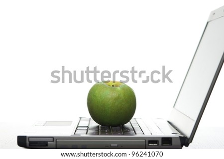 Open laptop sideways on with a fresh red apple creating a elearning concept. - stock photo
