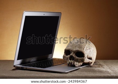 Open laptop with blank screen near human skull against nice brown background - stock photo