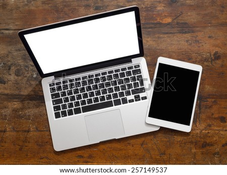 Open laptop with digital tablet, with isolated screen on old wooden desk - stock photo