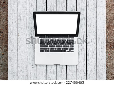 Open laptop with isolated screen on old wooden desk. - stock photo