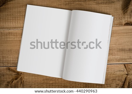 Open magazine with blank pages isolated on wooden table background - stock photo