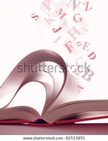 Open magic book with the letters - stock photo