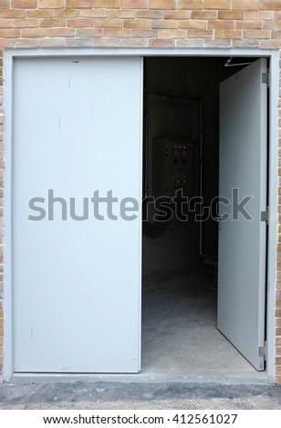 Open metal door of electricity room - stock photo
