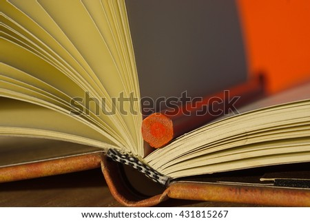 Open note book with orange pencil on a table - stock photo