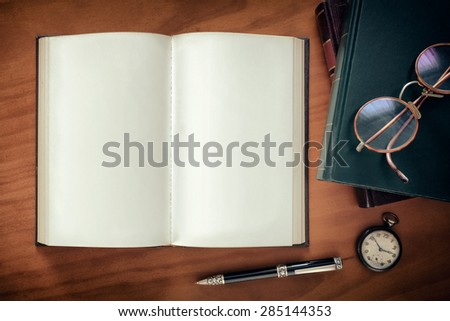 Open notebook, a pen and watch and a pair of glasses on top of books - stock photo