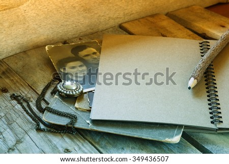 open notebook and antique photos on wooden table. retro filtered and toned image  - stock photo