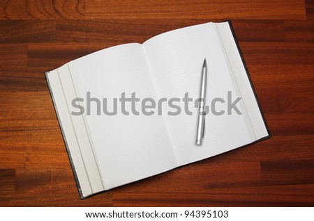 Open notebook and pen on a wooden table - stock photo
