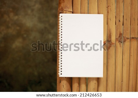 Open notebook on a table made �¢??�¢??of Bamboo. - stock photo