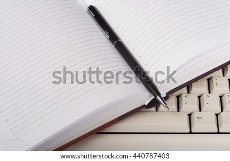 open notebook on the computer keyboard - stock photo