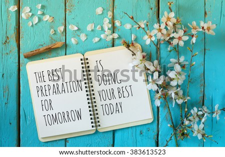 open notebook over wooden table with motivational saying the best preparation for tomorrow is doing your best today - stock photo