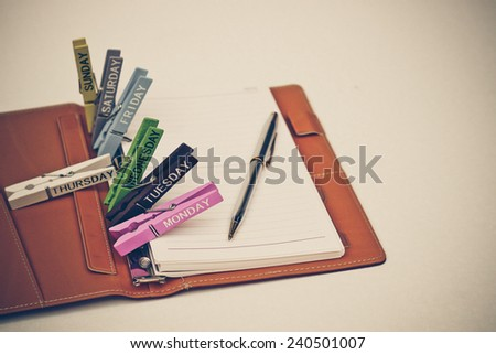 open notebook with a pen and wooden clips with days in a week on isolated background - stock photo