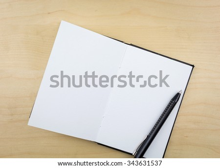 Open notebook with black pen, on wooden surface. - stock photo