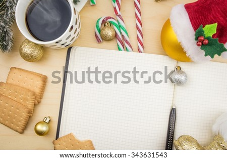 Open notebook with cup of coffee, cookies and winter festive ornaments. - stock photo