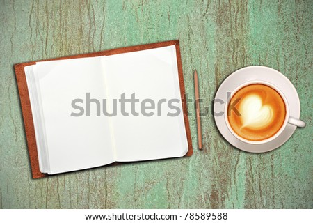 Open notebook with cup of coffee on green and brown background - stock photo
