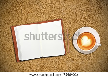 Open notebook with cup of coffee on sand - stock photo