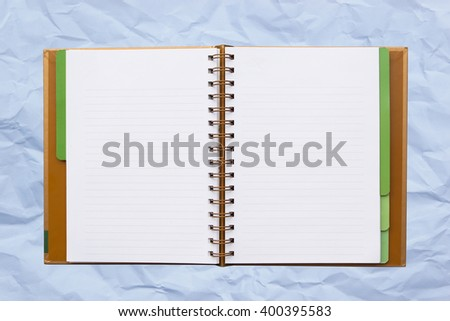 Open notebook with lined pages isolated on board background. - stock photo