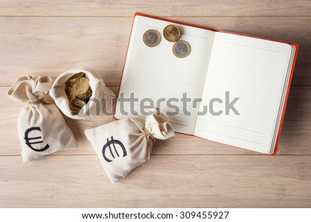 Open notebook with  money bags on wooden background - stock photo