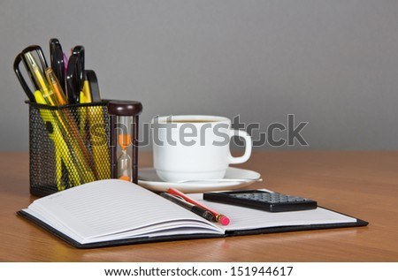 Open notepad, office accessories in a support the calculator, hourglasses and a cup of coffee on a table - stock photo