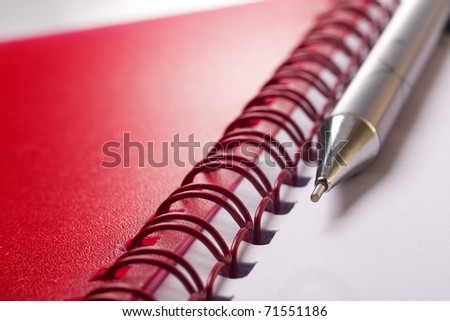 Open notepad with pen on white background - stock photo