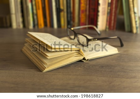 Open old book and glasses on table in library  - stock photo