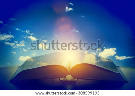 Open old book, light from the sky, heaven. Fantasy, imagination, education, religion concept.  - stock photo