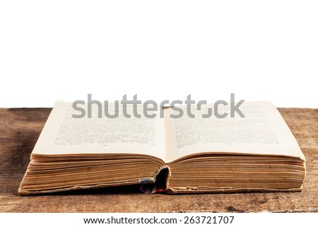 Open old book on a wooden desk isolated on white - stock photo