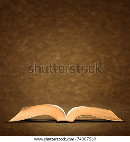 Open old book on brown background. - stock photo