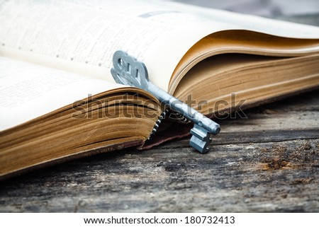 open old book on grunge wood desk with key - stock photo